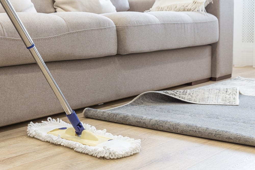 Cleaning floor with mop under carpet in living room, concept of good cleaning service